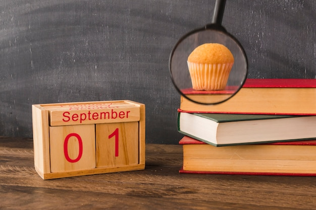 Magnifying glass near calendar and books with snack