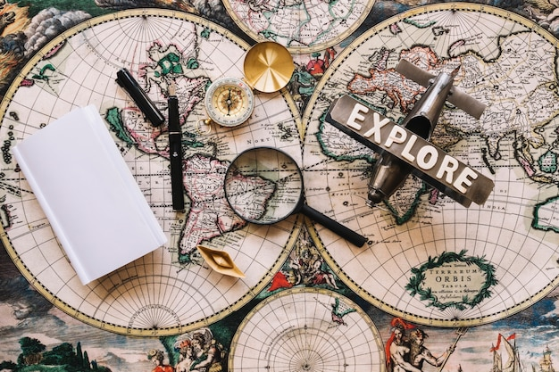 Magnifying glass near old compass and plane