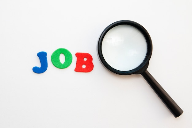 A magnifying glass near the word job done with letters on a white background,