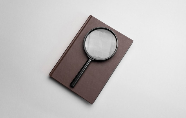 Magnifying glass and notebook on grey background.
