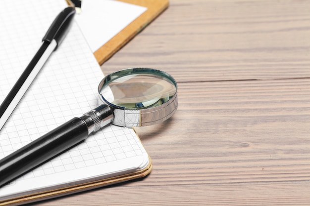 Magnifying glass and notebook on wooden table