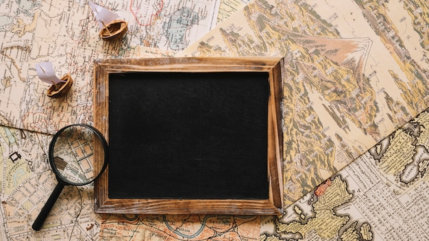 Magnifying glass and nutshell boats near chalkboard