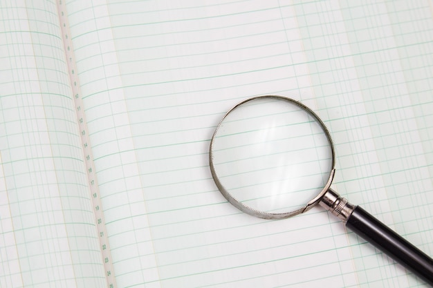 Увеличительное стекло на пустой бухгалтерской книге крупным планом