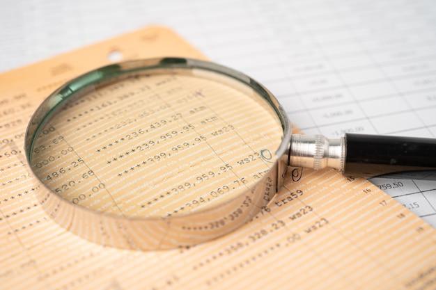 Увеличительное стекло на счетной книге банка