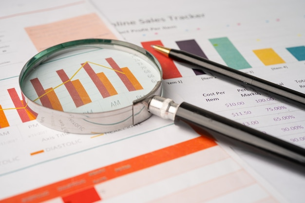 チャートグラフ紙の拡大鏡。金融開発、銀行口座、統計、投資分析研究データ経済、証券取引所取引、営業所会社会議のコンセプト。