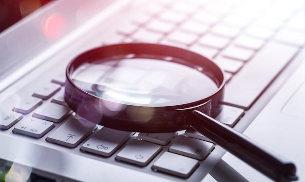 Увеличительное стекло на клавиатуре ноутбука крупным планом