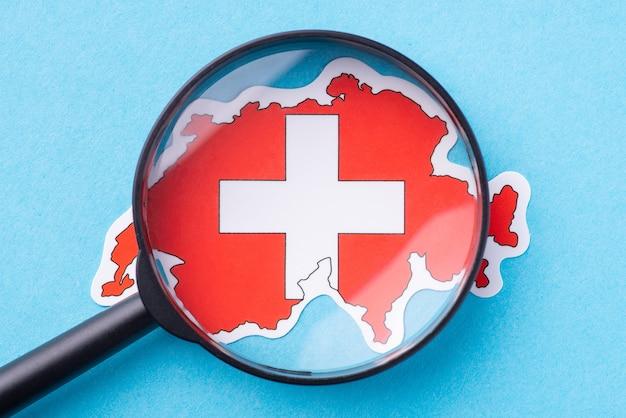 Увеличительное стекло на карте швейцарии. концепция поближе познакомиться с европейской страной, изучить ее культуру, традиции и религию.