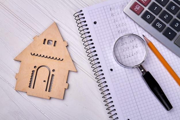 ノートと木造住宅のシルエットの虫眼鏡