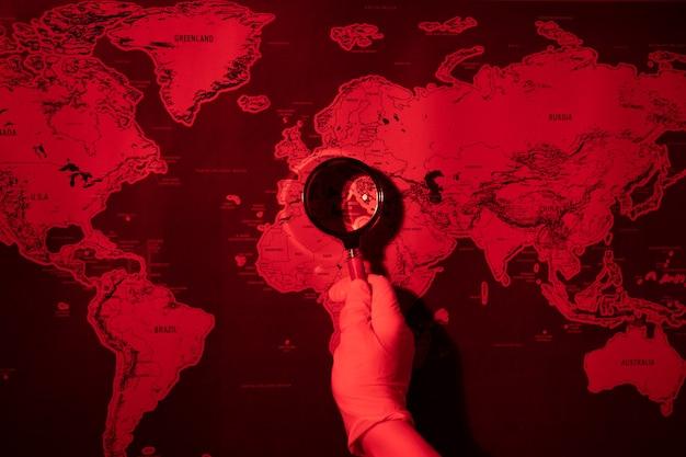Увеличительное стекло на тонированной красной карте, концепция мировой эпидемии