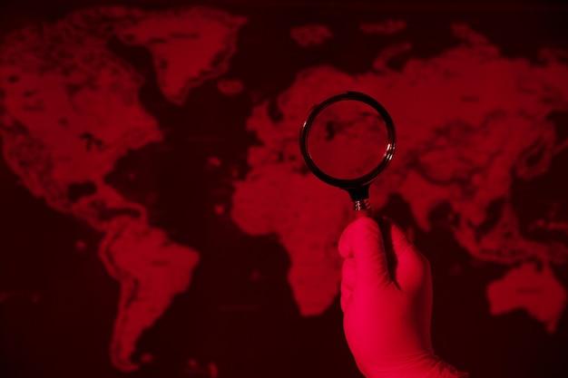 Увеличительное стекло на тонированной красной карте, концепция всемирной пандемии