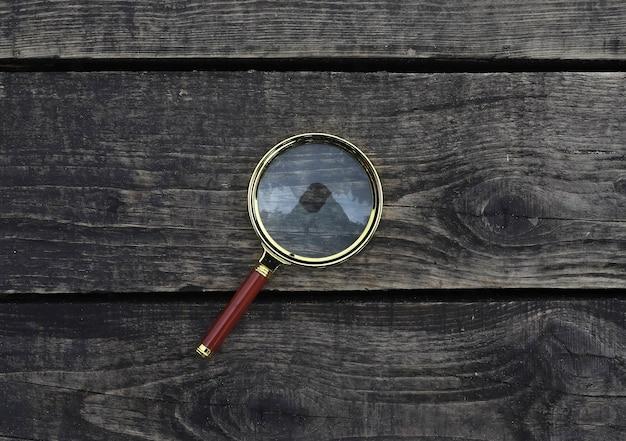 Увеличительное стекло на деревянной состаренной доске и увеличении фона древесины