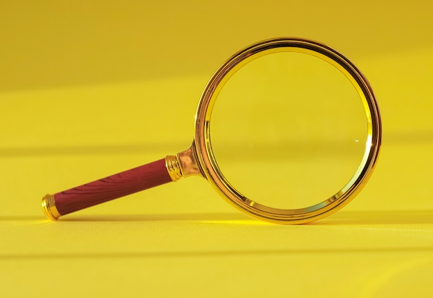 Увеличительное стекло на желтом фоне со светом и тенью
