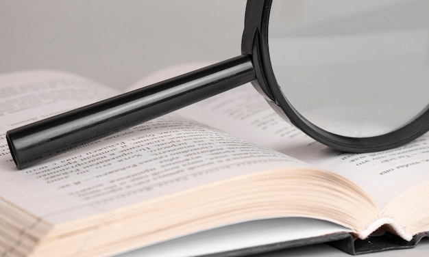 Magnifying glass on opened old book for searching and reading concept