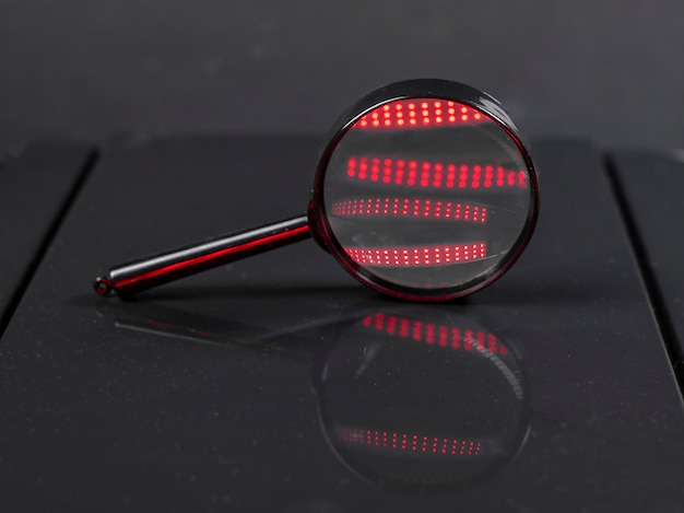빨간불 플레어가있는 어두운 검정색 배경에 돋보기 또는 줌 렌즈. 검색 및 탐정 개념.