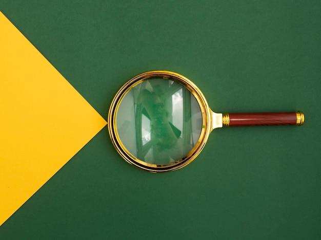 통찰력 발견과 지느러미의 상징으로 노란색 종이 빔과 녹색 배경 위에 돋보기.