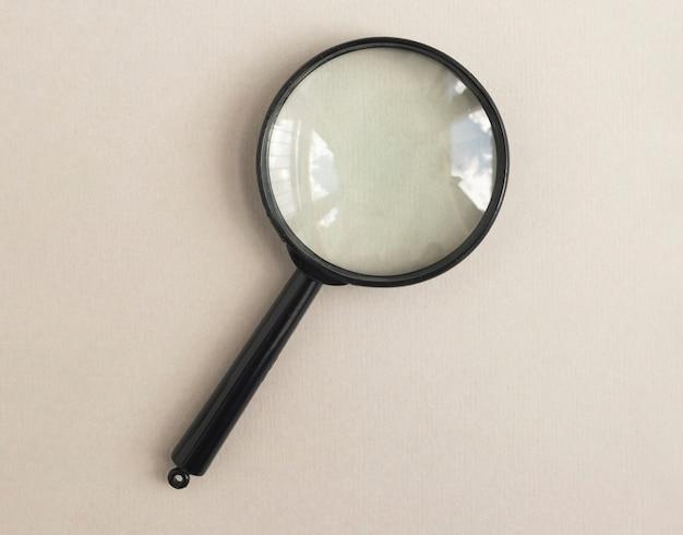 Увеличительное стекло на бледно-бежевом фоне лупа как концепция поиска ответов