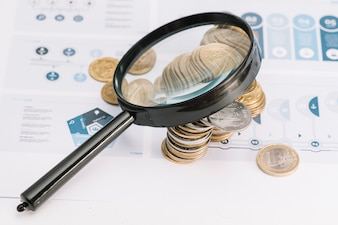 Magnifying glass over the coins on infographic template