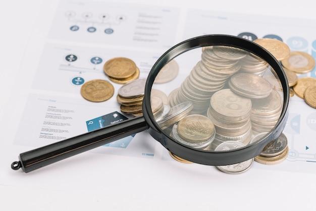 Увеличительное стекло над упавшими монетами на инфографическом шаблоне