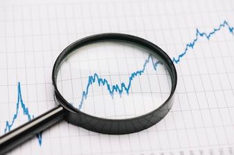 Увеличительное стекло над графиком фондового рынка на бумаге
