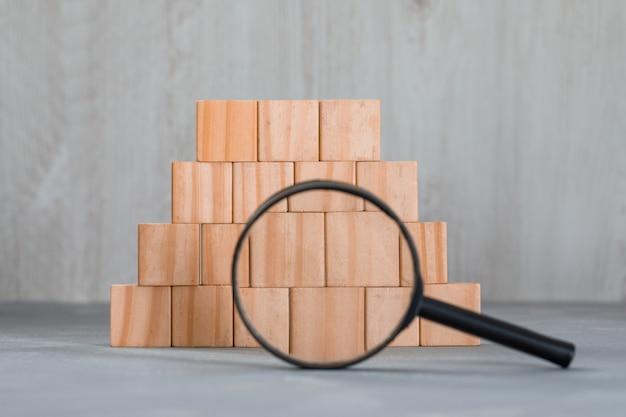 석고와 나무 테이블에 쌓인 나무 큐브 위에 돋보기