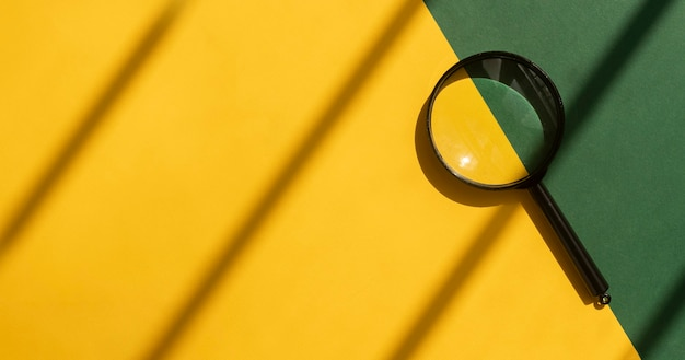 복사 공간 노란색과 녹색 배경 위에 돋보기. copyspace와 햇볕이 잘 드는 밝은 배경에서 검색 도구입니다.