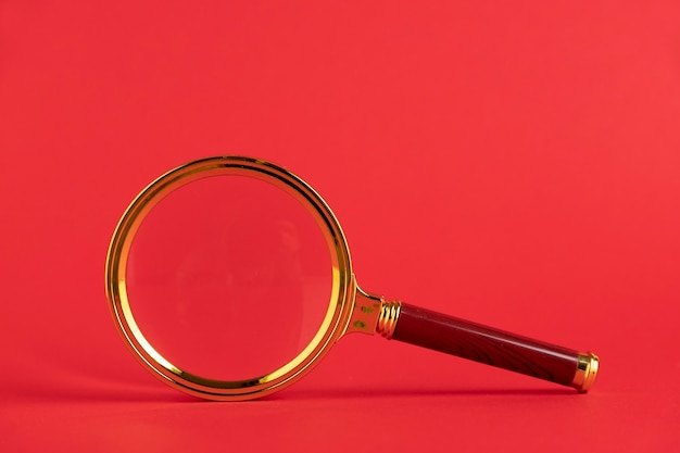 Magnifying glass on a red background. copy space.