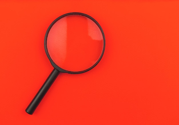Magnifying glass on a red background isolated, top view photo