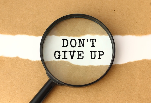 The magnifying glass reveals the don't give up text appearing behind the torn brown paper.