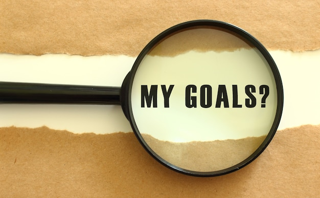 The magnifying glass reveals the my goals text appearing behind the torn brown paper.
