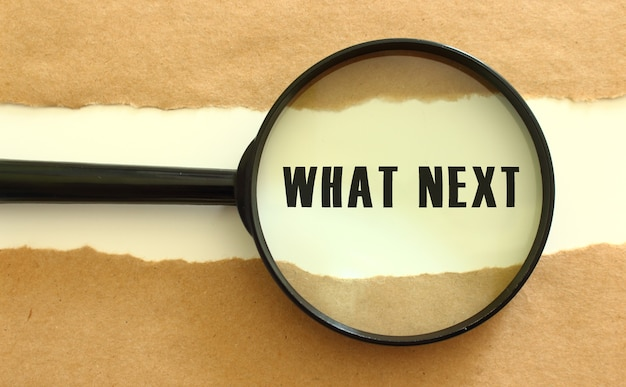The magnifying glass reveals the what next text appearing behind the torn brown paper. business concept