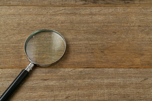 A magnifying glass on shabby wooden board.