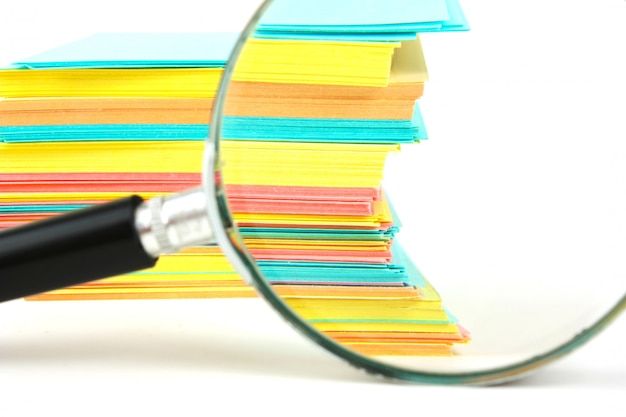 Magnifying glass and a stack of paper for notes