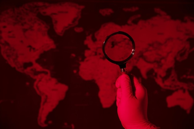 Magnifying glass on toned red  map, world pandemic concept