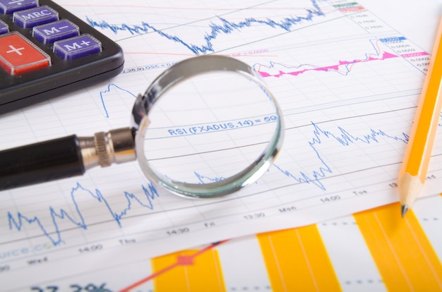 Magnifying glass on top of financial market info