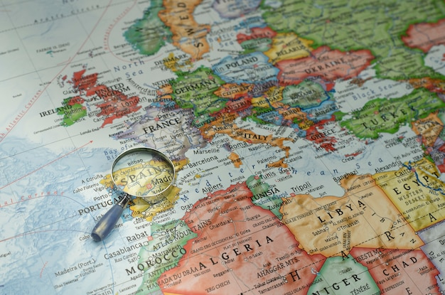 Magnifying glass towards spain on a worldwide map