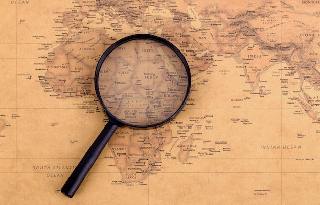 Magnifying glass on vintage map. travel and adventure concept.