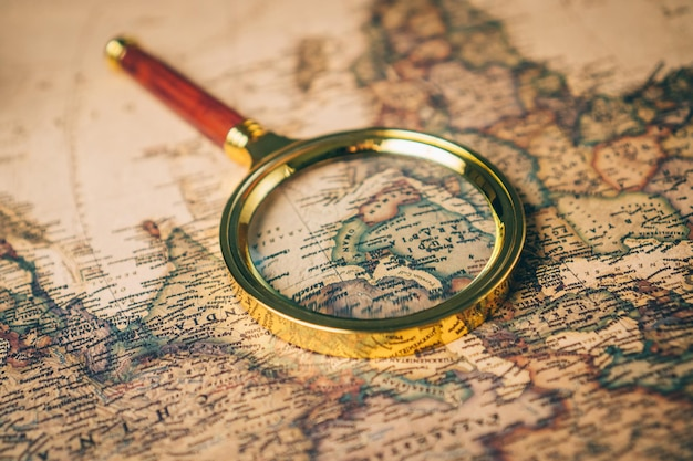 Magnifying glass on a vintage world map