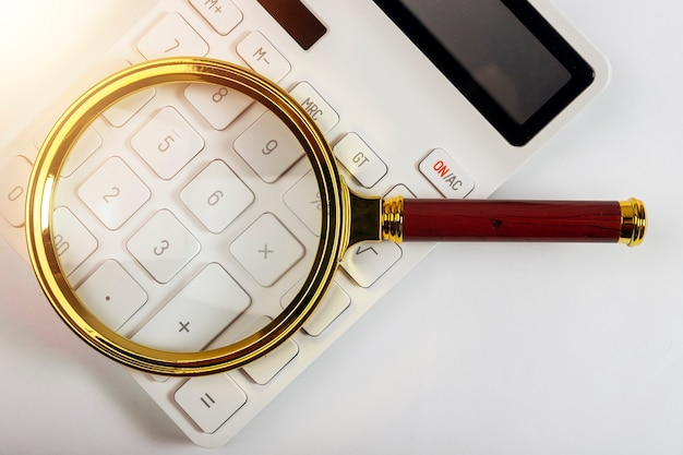 Magnifying glass on white calculator, analysis and accounting concept.