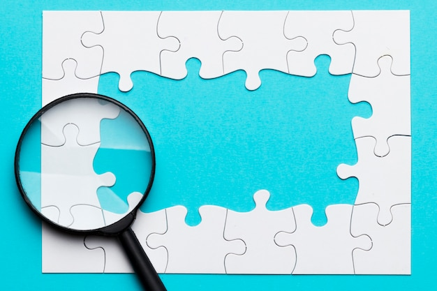 Magnifying glass over white jigsaw puzzle frame over blue surface