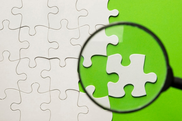 Magnifying glass over white jigsaw puzzle on green backdrop