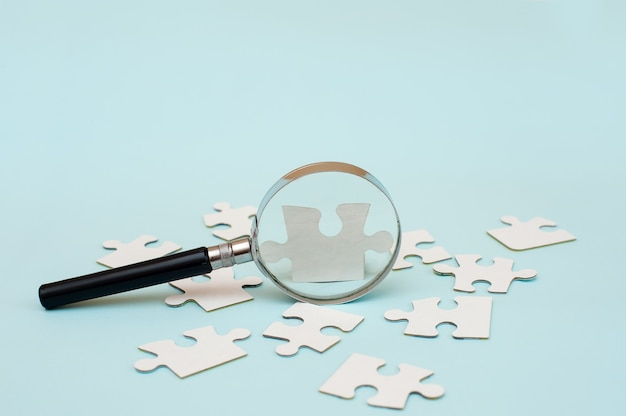 Magnifying glass and white puzzle on blue background
