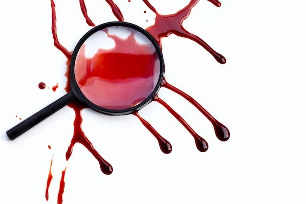 白い背景の上の血と拡大鏡。