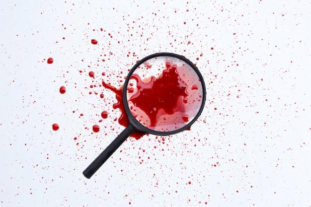 白い表面に血の付いた虫眼鏡。