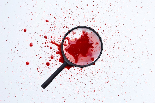 Magnifying glass with blood on white surface.