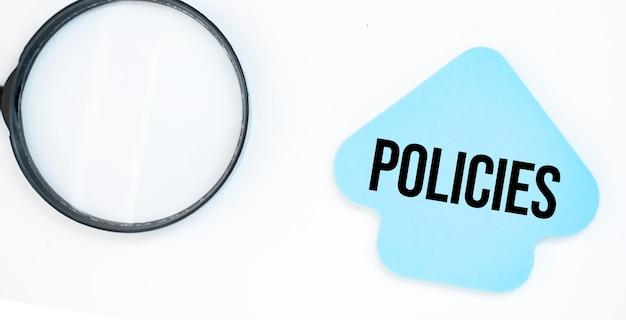 テキスト付きの青い矢印の紙シート付きの虫眼鏡ポリシー
