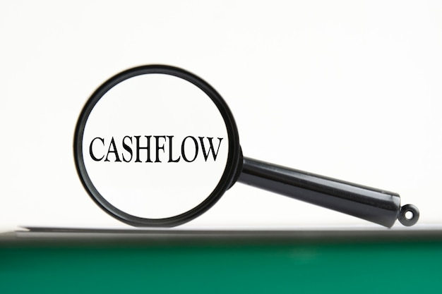 녹색 페이지, 흰색 배경이 있는 노트북에 텍스트 cashflow가 있는 돋보기