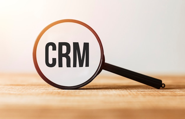 Magnifying glass with text crm on wooden table.