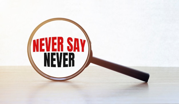 Magnifying glass with text never say never on wooden table.