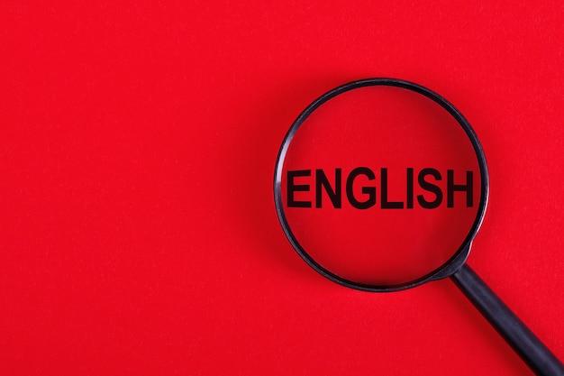 赤い背景に英語の碑文が付いた虫眼鏡。