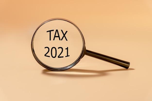 Tax2021という言葉が付いた虫眼鏡。ビジネスと税の概念